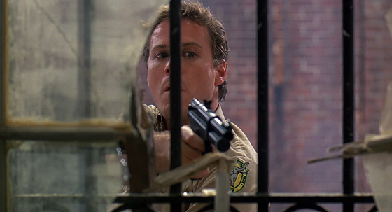 Oliver (John Heard) prepares to tranquilize a deadly panther.