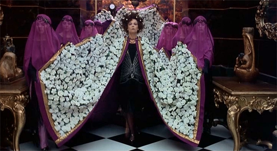 """""""Every day is Halloween in Tinseltown"""": Alla Nazimova (Leslie Caron) arrives at Valentino's funeral with style."""