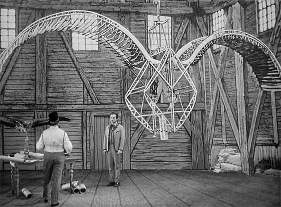 Simon Hart (Lubor Tokos) is shown a flying machine in the Count's island lair.