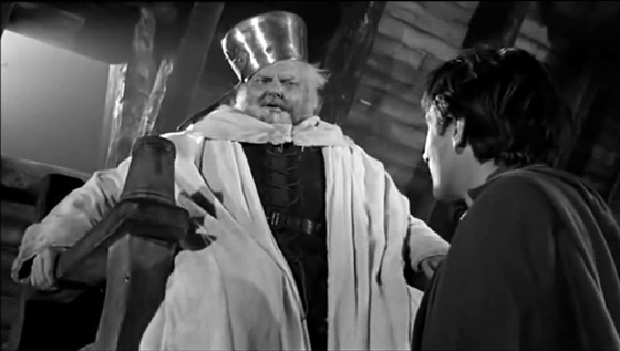 Falstaff (Orson Welles) impersonates the King for the amusement of Prince Hal (Keith Baxter).