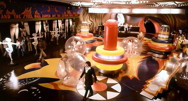 Jerry Cornelius (Jon Finch)  strides through a pinball arcade.