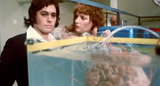 Jerry and Miss Brunner (Jenny Runacre) inside her secret laboratory.