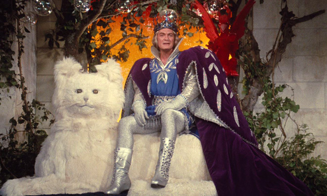 Jean Marais as the Blue King, sitting on his throne.