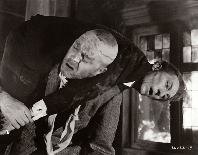 Publicity still: Freddie Jones carries Cushing back into a burning building.