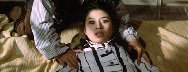 Keiko (Kayo Matsuo) is held down by Genzo while Dr. Yamaguchi approaches her with a hypodermic needle.