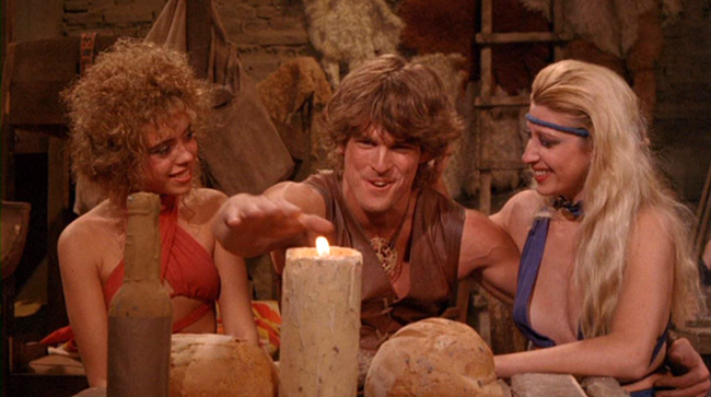 Deathstalker (John Terlesky) shows off to some tavern wenches by passing his hand through a flame. They're impressed.