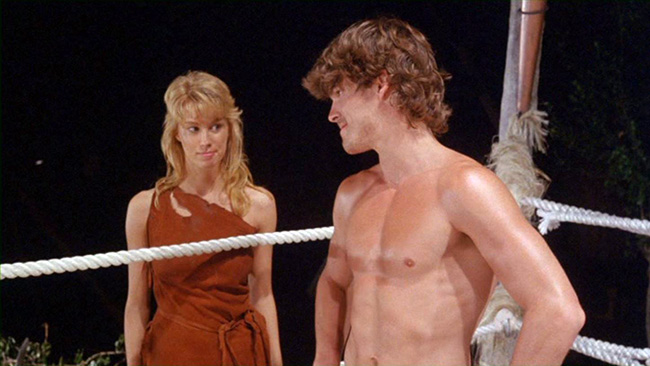 Reena (Monique Gabrielle) watches as Deathstalker prepares for a wrestling match with an Amazon.