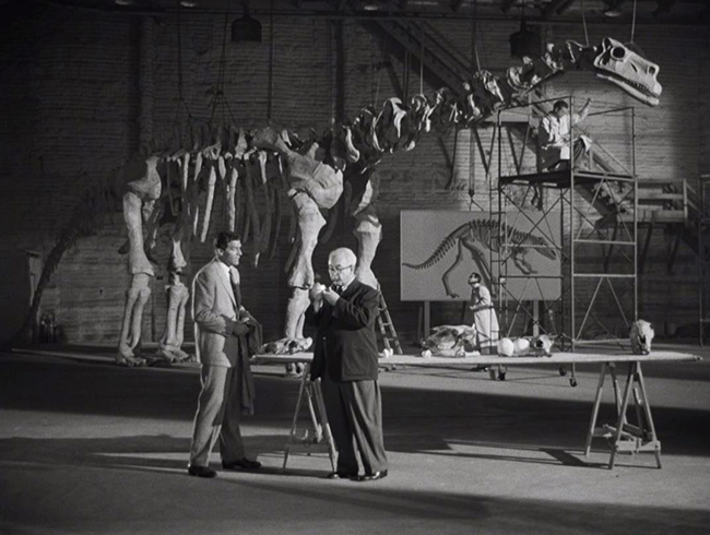 "Prof. Thomas Nesbitt (Paul Hubschmid) describes the Rhedosaurus to Prof. Thurgood Elson (Cecil Kellaway). The skeleton in the background was borrowed from ""Bringing Up Baby."""