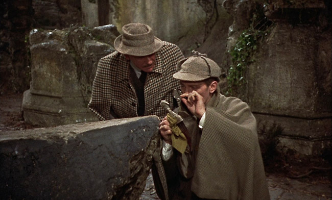 Sherlock Holmes (Peter Cushing) examines a dagger while Dr. Watson looks on.