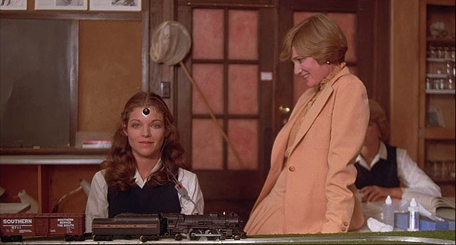 Gillian (Amy Irving) tests her psychic abilities on a model train.
